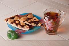 Φλυτζάνι του κέικ τσαγιού και δαμάσκηνων με το ψίχουλο σε χαρτί περγαμηνής Στοκ Φωτογραφίες