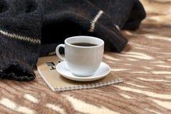 Φλυτζάνι του καυτού καφέ σε ένα κάλυμμα στοκ εικόνα