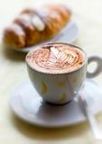 Φλυτζάνι του καυτού cappuccino με brioche Στοκ φωτογραφία με δικαίωμα ελεύθερης χρήσης
