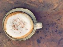 Φλυτζάνι του καυτού cappuccino πέρα από το γάλα αφρού στον ξύλινο πίνακα Στοκ Φωτογραφία