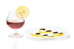 Φλυτζάνι του κονιάκ με το πρόχειρο φαγητό λεμονιών Στοκ εικόνα με δικαίωμα ελεύθερης χρήσης
