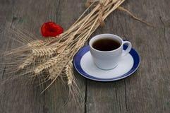 Φλυτζάνι του μαύρου καφέ, δέσμη των σιταρένιων αυτιών και λουλούδι της παπαρούνας Στοκ Φωτογραφία