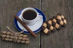 Φλυτζάνι του μαύρου καφέ και δύο σειρές των μπισκότων στο shabby υπολογιστή γραφείου Στοκ Εικόνα