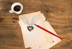 Φλυτζάνι του μαύρου καφέ με την καρδιά φασολιών καφέ με τα φτερά που επισύρονται την προσοχή στο μολύβι και τον κόκκινο στυλό σε  Στοκ Φωτογραφία