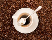 Φλυτζάνι του μαύρου καφέ πέρα από καλυμμένο το φασόλι υπόβαθρο Στοκ εικόνα με δικαίωμα ελεύθερης χρήσης