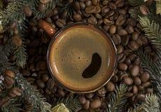 Φλυτζάνι του μαύρου καφέ, φασόλια καφέ, κομψοί κλάδοι, εξυπηρέτηση, Δεκέμβριος στοκ εικόνα