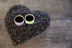 Φλυτζάνι του μαύρων καφέ και των φασολιών καφέ στο ξύλινο υπόβαθρο Στοκ φωτογραφία με δικαίωμα ελεύθερης χρήσης