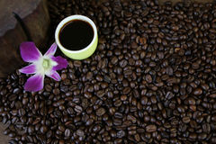 Φλυτζάνι του μαύρων καφέ και των φασολιών καφέ στο ξύλινο υπόβαθρο Στοκ Φωτογραφίες