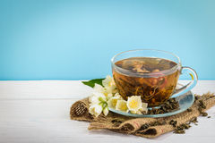 Φλυτζάνι του πράσινου τσαγιού με jasmine τα λουλούδια στο ξύλινο υπόβαθρο στοκ εικόνες