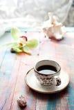 Φλυτζάνι του συνόλου espresso με ένα λουλούδι και τα θαλασσινά κοχύλια ορχιδεών Στοκ Φωτογραφίες