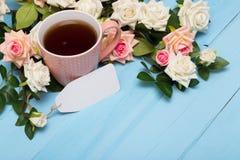 Φλυτζάνι του τσαγιού, ανθοδέσμη, τριαντάφυλλα, κάρτα στο ξύλινο υπόβαθρο Στοκ φωτογραφία με δικαίωμα ελεύθερης χρήσης