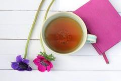 Φλυτζάνι του τσαγιού και των λουλουδιών με το ρόδινο σημειωματάριο Στοκ φωτογραφίες με δικαίωμα ελεύθερης χρήσης