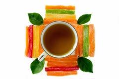 Φλυτζάνι του τσαγιού με τα γλασαρισμένα φρούτα ανανά και τα πράσινα φύλλα σε ένα W Στοκ φωτογραφία με δικαίωμα ελεύθερης χρήσης