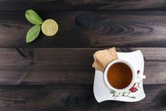 Φλυτζάνι του τσαγιού με τα μπισκότα τσαγιού και του φρέσκου ασβέστη στον ξύλινο πίνακα Στοκ φωτογραφία με δικαίωμα ελεύθερης χρήσης