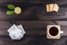 Φλυτζάνι του τσαγιού με τα μπισκότα τσαγιού, τον ασβέστη και τις τσάντες τσαγιού στον ξύλινο πίνακα Στοκ Εικόνες