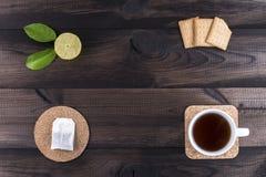 Φλυτζάνι του τσαγιού με τα μπισκότα τσαγιού, το φρέσκους ασβέστη και την τσάντα τσαγιού σε woodentable Στοκ Φωτογραφία