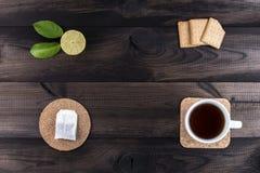 Φλυτζάνι του τσαγιού με τα μπισκότα τσαγιού, το φρέσκους ασβέστη και την τσάντα τσαγιού στον ξύλινο πίνακα Στοκ φωτογραφίες με δικαίωμα ελεύθερης χρήσης