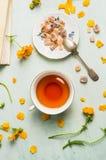Φλυτζάνι του τσαγιού με την καφετιά ζάχαρη και τα λουλούδια candi Στοκ Φωτογραφίες