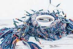 Φλυτζάνι του τσαγιού που τυλίγεται στο θερμό υφαμένο μαντίλι που διακοσμείται με τα φω'τα νεράιδων Στοκ φωτογραφία με δικαίωμα ελεύθερης χρήσης