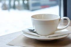 Φλυτζάνι του τσαγιού σε έναν ξύλινο πίνακα στο εστιατόριο άσπρος χειμώνας ανασκόπησης Στοκ Φωτογραφία