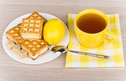 Φλυτζάνι του τσαγιού στην πετσέτα, τα μπισκότα, το λεμόνι και την άμορφη ζάχαρη Στοκ φωτογραφία με δικαίωμα ελεύθερης χρήσης