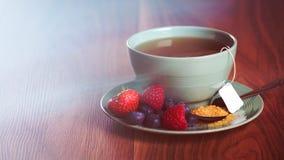Φλυτζάνι του τσαγιού φρούτων με τις φράουλες, τα σμέουρα και τα βακκίνια στον ξύλινο πίνακα, με το διάστημα αντιγράφων Στοκ Φωτογραφία