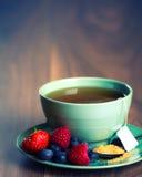 Φλυτζάνι του τσαγιού φρούτων με τις φράουλες, τα σμέουρα και τα βακκίνια στον ξύλινο πίνακα, με το διάστημα αντιγράφων Στοκ Φωτογραφίες