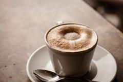 Φλυτζάνι του cappuccino πέρα από τον ξύλινο πίνακα Στοκ Φωτογραφία