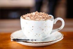 Φλυτζάνι του cappuccino που ψεκάζεται με την ξυμένη σοκολάτα Στοκ Εικόνες