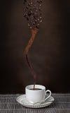 Φλυτζάνι του espresso με ένα whirlwind των φασολιών καφέ Στοκ Εικόνες