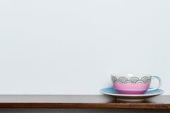 Φλυτζάνι τσαγιού στον ξύλινο άσπρο τοίχο ραφιών στον τόνο vintange Στοκ φωτογραφία με δικαίωμα ελεύθερης χρήσης
