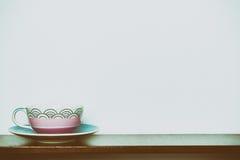 Φλυτζάνι τσαγιού στον ξύλινο άσπρο τοίχο ραφιών στον τόνο vintange Στοκ Εικόνες
