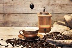 Φλυτζάνι, φασόλια και μύλος καφέ μπροστά από το εκλεκτής ποιότητας ξύλινο backgr Στοκ φωτογραφία με δικαίωμα ελεύθερης χρήσης