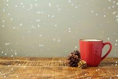 Φλυτζάνι χειμερινού κόκκινο καφέ με το καλαμπόκι πεύκων Στοκ Φωτογραφίες