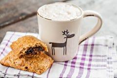 Φλυτζάνι Cappuccino με τα ελάφια Χριστουγέννων και muffin με τη σοκολάτα επάνω Στοκ φωτογραφία με δικαίωμα ελεύθερης χρήσης
