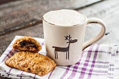 Φλυτζάνι Cappuccino με τα ελάφια Χριστουγέννων και muffin με τη σοκολάτα επάνω Στοκ Εικόνες