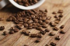 Φλυτζάνι cappuccino με τα ψημένα φασόλια καφέ στον ξύλινο πίνακα Στοκ Εικόνα