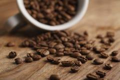 Φλυτζάνι cappuccino με τα ψημένα φασόλια καφέ στον ξύλινο πίνακα Στοκ Εικόνες