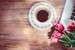 Φλυτζάνι, lap-top και λουλούδια καφέ στον ξύλινο πίνακα Εκλεκτής ποιότητας επίδραση Στοκ Εικόνες