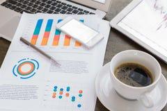 Φλυτζάνι lap-top, ταμπλετών, smartphone και καφέ με το οικονομικό docume Στοκ φωτογραφίες με δικαίωμα ελεύθερης χρήσης