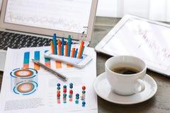 Φλυτζάνι lap-top, ταμπλετών, smartphone και καφέ με το οικονομικό docume Στοκ φωτογραφία με δικαίωμα ελεύθερης χρήσης
