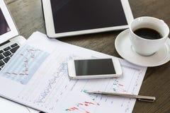 Φλυτζάνι lap-top, ταμπλετών, smartphone και καφέ με το οικονομικό docume Στοκ εικόνα με δικαίωμα ελεύθερης χρήσης