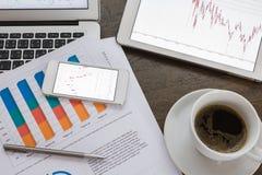 Φλυτζάνι lap-top, ταμπλετών, smartphone και καφέ με το οικονομικό docume Στοκ Φωτογραφίες