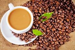 Φλυτζανιών και arabica καφέ φασόλια στο σάκο υφασμάτων Στοκ Εικόνα