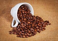 Φλυτζανιών και arabica καφέ φασόλια στο σάκο υφασμάτων Στοκ Φωτογραφία