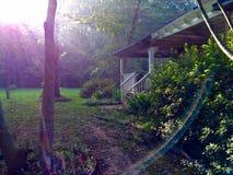 Φλόγα φακών μια ηλιόλουστη ημέρα, μπροστά από ένα σπίτι στοκ εικόνα