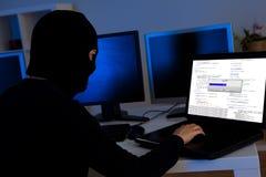Χάκερ που μεταφορτώνει τις πληροφορίες από έναν υπολογιστή Στοκ Φωτογραφίες