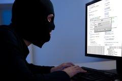 Χάκερ που μεταφορτώνει τις πληροφορίες από έναν υπολογιστή Στοκ Φωτογραφία