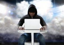 Χάκερ που χρησιμοποιεί ένα lap-top μπροστά από το νεφελώδες υπόβαθρο Στοκ εικόνες με δικαίωμα ελεύθερης χρήσης
