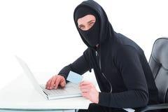 Χάκερ που χρησιμοποιεί το lap-top και την πιστωτική κάρτα Στοκ Φωτογραφία